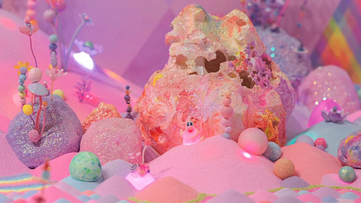 An colorful art installation using fluorescent color sand in multiple piles, with tiny decorations emerging from them